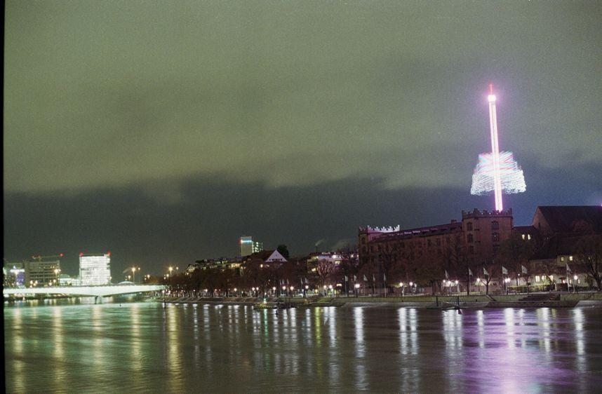 Basel. Blick von der Mittleren Brücke auf die Kaserne. Langzeitbelichtung eines Herbstmesse-Fahrgeschäfts.