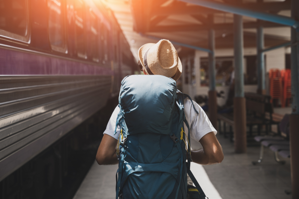 Male traveler with backpack walking next to a train he needs to catch
