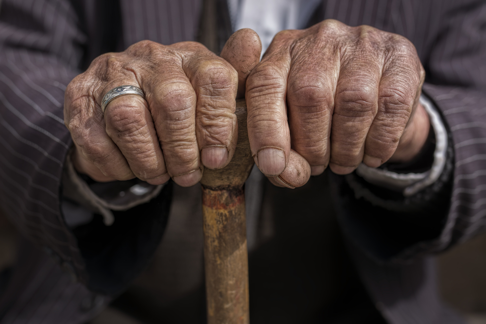 hands of old man holding a cane